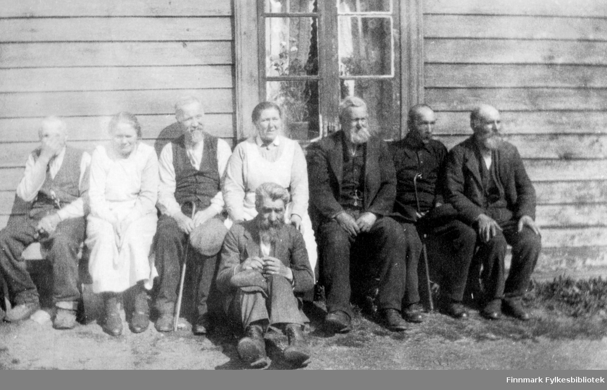 Fotografi av ukjente personer. To kvinner og seks eldre menn. De sitter på en benk med ryggen til et trehus. Det er et vindu med hvite gardiner og blomster, på veggen. En mann sitter foran på bakken. De fleste av mennene har skjegg, og er mørkkledte. To av dem har stokk. Kvinnene har hvite forklekjoler på seg