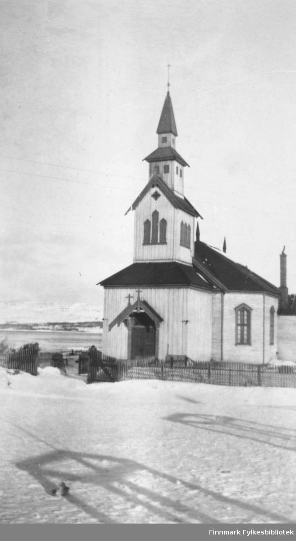 Fotografi av Kirkenes kirke. Det er et tregjerde rundt kirken. Det ligger snø på bakken. I bakgrunnen ser vi sjøen og fjell