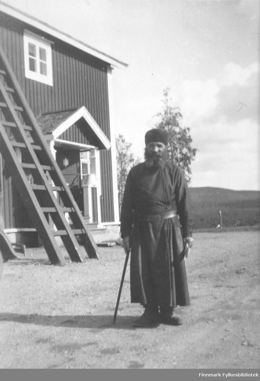 Fotografi av en munk. Han har skjegg og er kledt i en mørk kjortel. På hodet har han en mørk munkelue og i hånden holder han en stav. Mannen står utenfor et trehus, med hvite lister. Det står en stige opp mot veggen. På døren er det et merke eller skilt. I bakgrunnen ser man mot fjell og skog. Det står noen høye trær ved siden av huset