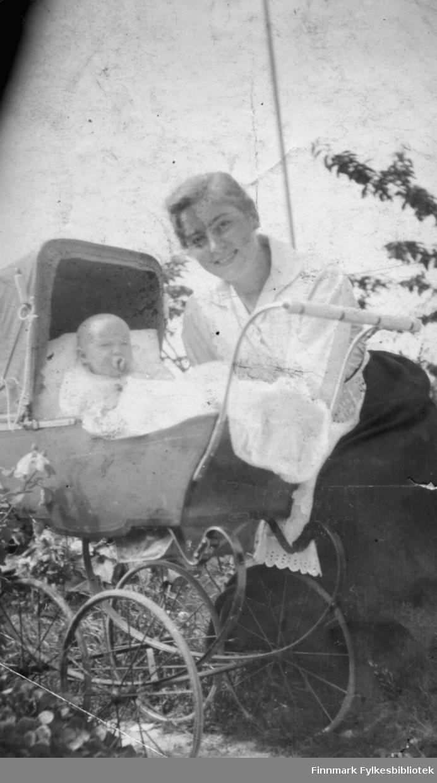 Fotografi av ei kvinne med et barn i ei barnevogn. Kvinnen er kledt i en hvit bluse og et svart skjørt med et hvitt forklæ. Barnet sitter i vognen og har noe i munnen. Det er et hvitt teppe over barnet