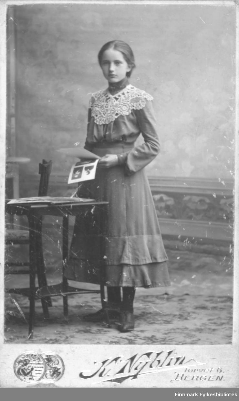 Portrett av ei ukjent jente som står ved siden av et bord. I hånden holder hun noen bilder. Hun er kledt i en kjole med kappe på skjørtet. Rundt halsen har hun en stor hvit krage