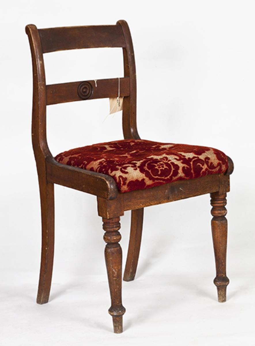 Stol uten armlener. Setet trukket med rødt og lysegrått velurstoff. Dreide forben. Antatt sent attenhundretall.