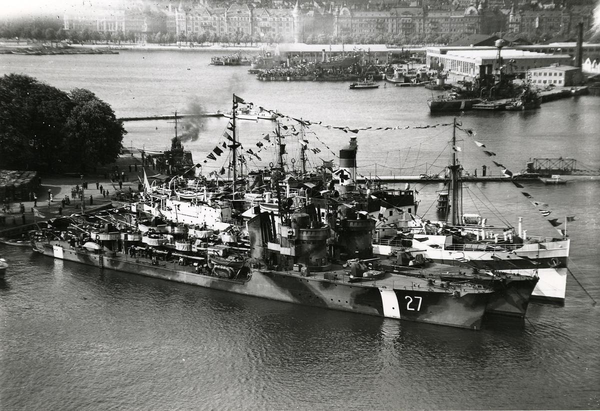I förgrunden: torpedbåtarna (kustjagarna) Romulus (27) och Remus (28). Bakom dem: Lasarettsfartyget Prins Carl. I bakgrunden vid Galärvarvet: ett gammalt avrustat pansarskepp troligen Äran, några äldre jagare, vedettbåtar m.m.