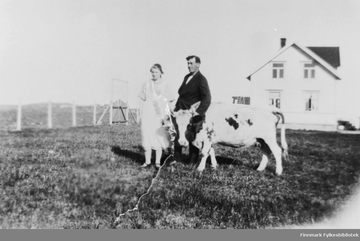 En mann, Rolf Fredriksen og en kvinne, Liva Hammer står på åkern foran Fredriksens hus. En ku poserer på biulset sammens med dem.
