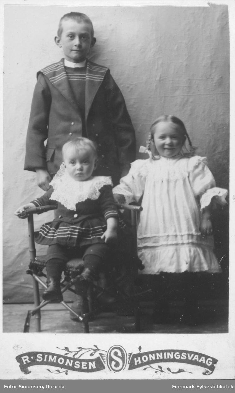 Portrett av tre barn: ung gutt i matrosdress jente med sløyfer og hvit kjole jente med mørk kjole sitter foran. i studio ateliere.  Albumet med bildet kommer fra Ekkerøy, kanskje de kommer derfra.