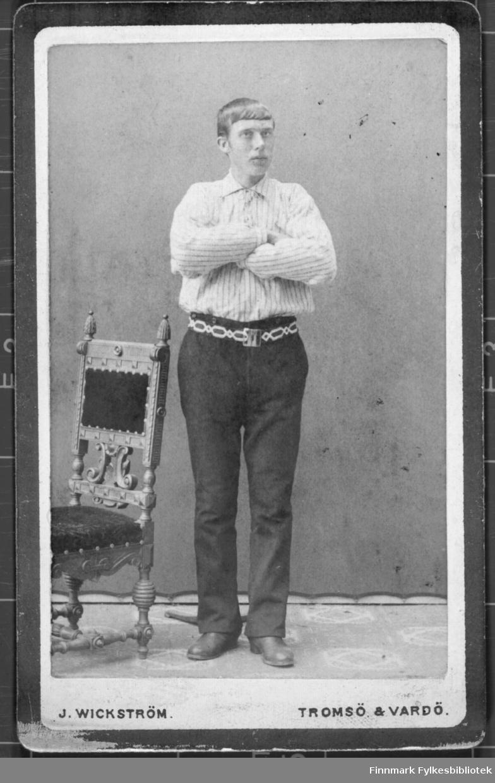 Portrett av en ung menn kledd i mørk bukse hvit skjorte armene i kryss. Mønstrete belte. Deler av en stol står til venstre i bildet.  Albumet med bildet kommer fra Ekkerøy, kanskje han kommer derfra.