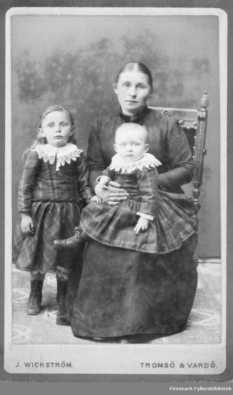 Familieportrett av en mor og hennes to barn tatt av Jørgen Wikström i Vardø. Kvinnen sitter med den minste jente i fanget, den andre jenten står ved sidan av henne. Jentene er kledd i like rutete kjoler med hvite broderte krager. Moren i en vanlig  mørk lang kjole. Albumet med bildet kommer fra Ekkerøy, kanskje familien bodde der.