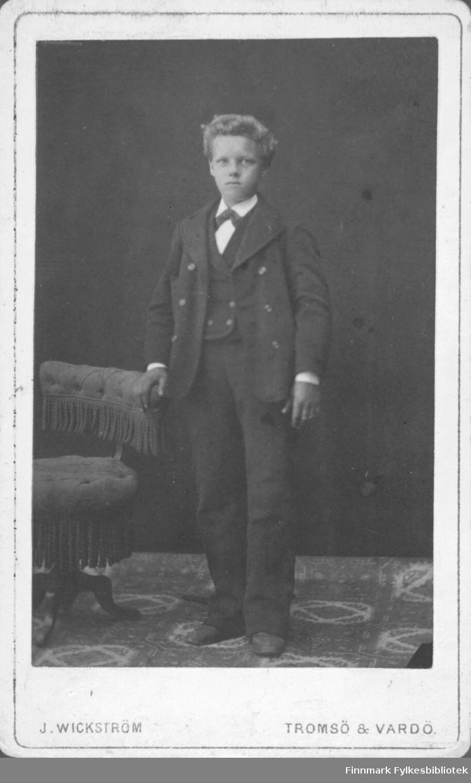 En ung gutt i mørk dress med vest, hvit skjorte og sløyfe. Det ligger et teppe på gulvet, han   hviler hånden på en stol med rufser. Bildet er fra studio ateliere Albumet med bildet kommer fra Ekkerøy, kanskje han bodde der.