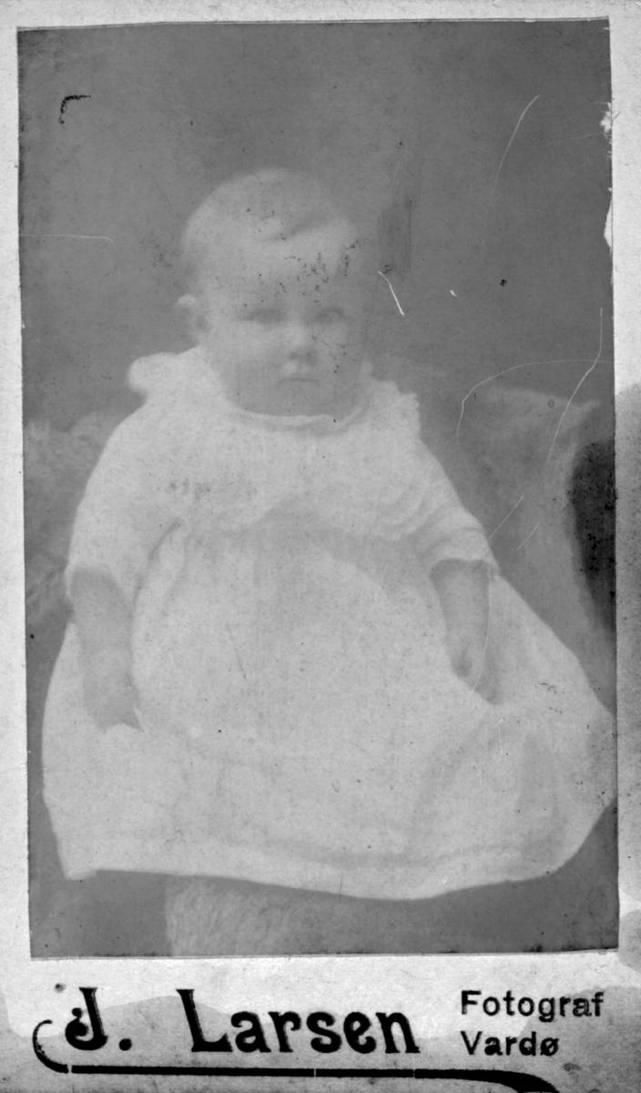 Et spedbarns portrett. Ingen opplysninger. Barnet har på seg en kjole. Bildet trolig tatt på slutten av 1800-tallet, begynnelsen av 1900-tallet.