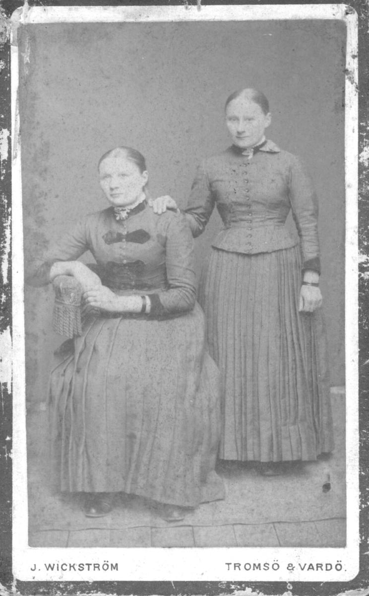 Portrett av Ida Johanne Ballo(Palo) og en ukjent kvinne. Ida sitter på stolen til venstre. De er begge kledd i kjoler. Bildet trolig tatt i 1890-årene, men dette er noe usikkert. Ida var originalt fra Vadsø men emigrerte senere til Amerika, trolig Detroit.
