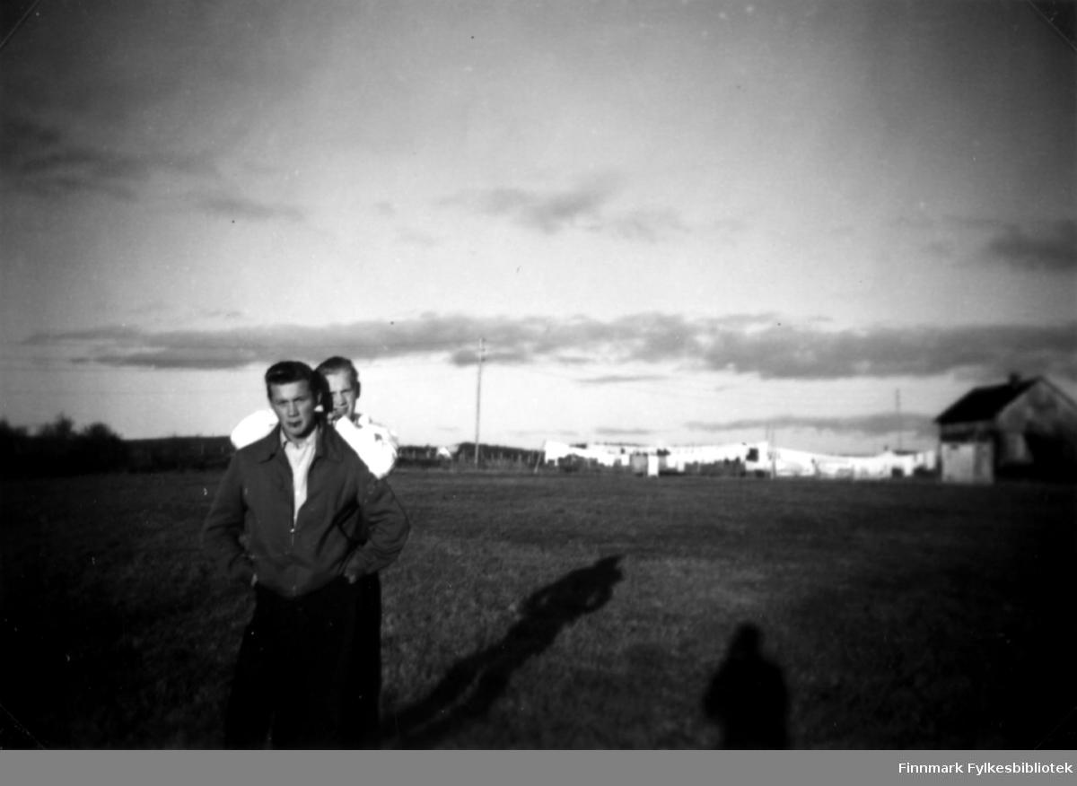 Fotografi av Olaf Stenbakk og Gunnar Bordi. De står ute på et tun. Bak dem til høyre står det et trehus. På snorene utenfor huset henger det klesvask