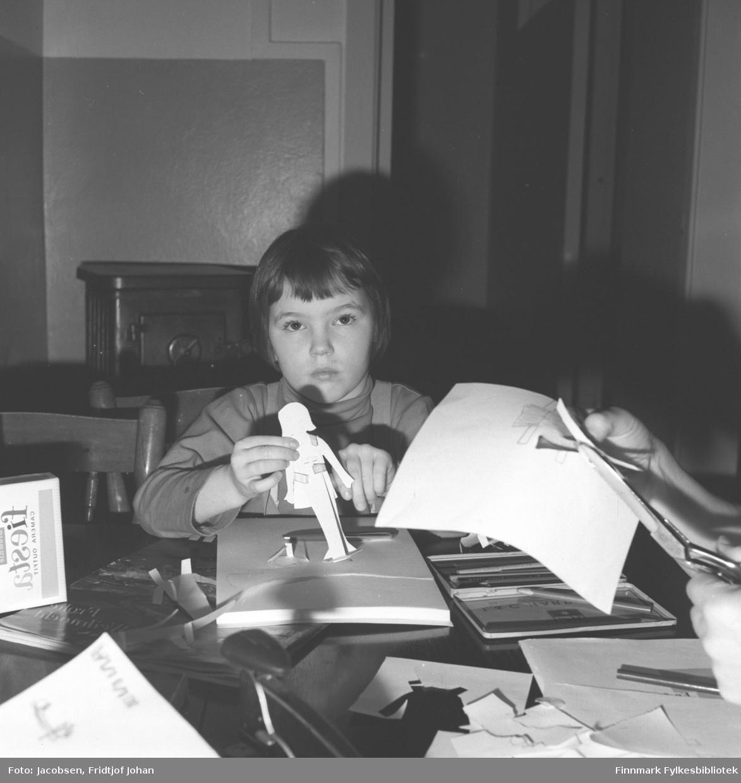 Eli Jacobsen sitter ved spisebordet hos tante og onkel Fridtjof og Aase Jacbosen og klipper ut papirfigurer.