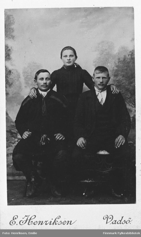 Tre ungdommer hos fotografen, fra venstre: Ole Mathisen sittende (kledd i samisk kofte), Aleksander Hansen sittende ved siden av han og Lydia Dørmænen (gift Jakola) stående bak dem. Lydia har lagt hendene på guttenes skuldre. I bakrunnen er et landskapsmaleri, bildet er tatt i atelier