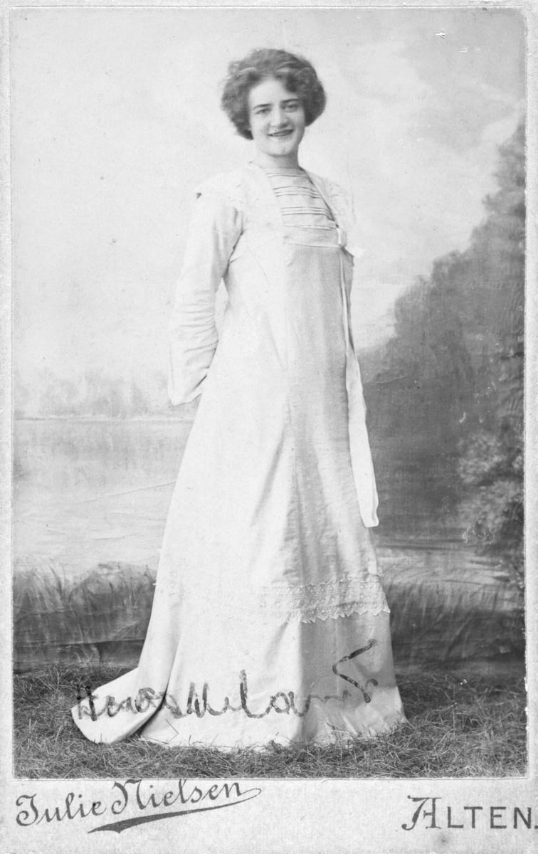 """Portrett av Astrid Froskeland, født 1887 i Alten (Alta).  Astrid står i hvit kjole foran en malt landskapskulisse med tørt gressdekke i bunnen av bildet. Bildet kan være tatt ute eller så forsøker fotografen å illudere sommer i fotostudio, noe den hvite kjolen også antyder. Bildet er tatt i Alten (Alta) av fotograf Julie Nielsen. Astrid er registrert som """"Butik og kontordame Telefonbestyrerinde"""" i folketelling for 1910, da bor hun i Kvænangen i Troms, adresse Vasnes-Kviteberg, Alteidet søndre, gårdsnummer 11, bruksnr. 1. Hun jobber da for """"Landhandler og gårdbruker"""" Henrik Mathias Giæver, født i Kvænangen.  Astrid er datter av Amtsskolebestyrer i Vadsø, John Andreas Johansen Froskeland , født 1849 i Hadsel, Nordland og Elise Johanna Froskeland fra Vardø, født 1877. Søsken: John Froskeland (1885) født i Vadsø og Alf Froskeland (1890) født i Alta.  Preus Museum har følgende opplysninger om fotografen: Født 06.02.1873. Død i Trondheim. Bosatt i Alta. Datter av Didrik August Nielsen og Magda, f. Dyblie. Gift i 1905 med Henry Kjeldsberg, 3 sønner og 1 dattter. Fotograf, organist og aktivt med i organisasjons- og foreningsliv."""
