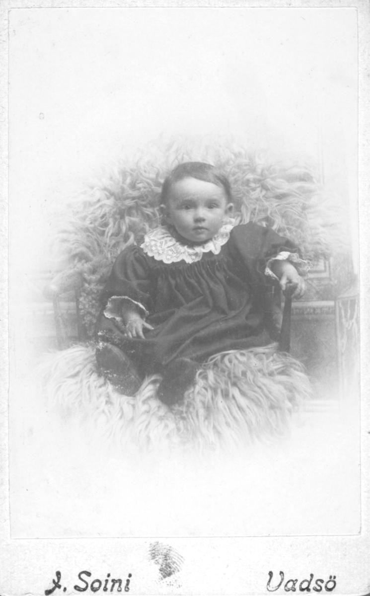 """Portrett av en liten jente,  Esther Johansen. Esther er kledd i mørk kjole med en vakker, hvit kniplingkrage i halsen. Hun er plassert i en pinnestol på et saueskinn. Hun har sko på bena. Fotograf Jasper Soini i Vadsø har fotografert Ester Johansen. Esther er i  folketellingen i 1910 i Vadsø  notert som Ester Johansen, født 23.07.1901, datter av bakermester Arvid Johansen (født 27.10.1871 i Vadsø)  og husmor Hilma Johansen (født 13.11.1872 i Seffle, Sverige). De bor i Kirkegate 58, i Vadsø. Trond Ballo har kommentert bildet: """"Ester Lovise Johansen, datter av bakermester Johan Arvid (Jonas) Johansen fra Vadsø og moren Hilma Emilia Janson fra Tveta i Värmland, Sverige. Ester Lovise giftet seg i 1931 i Vadsø med Thorleif Tønnessen."""""""
