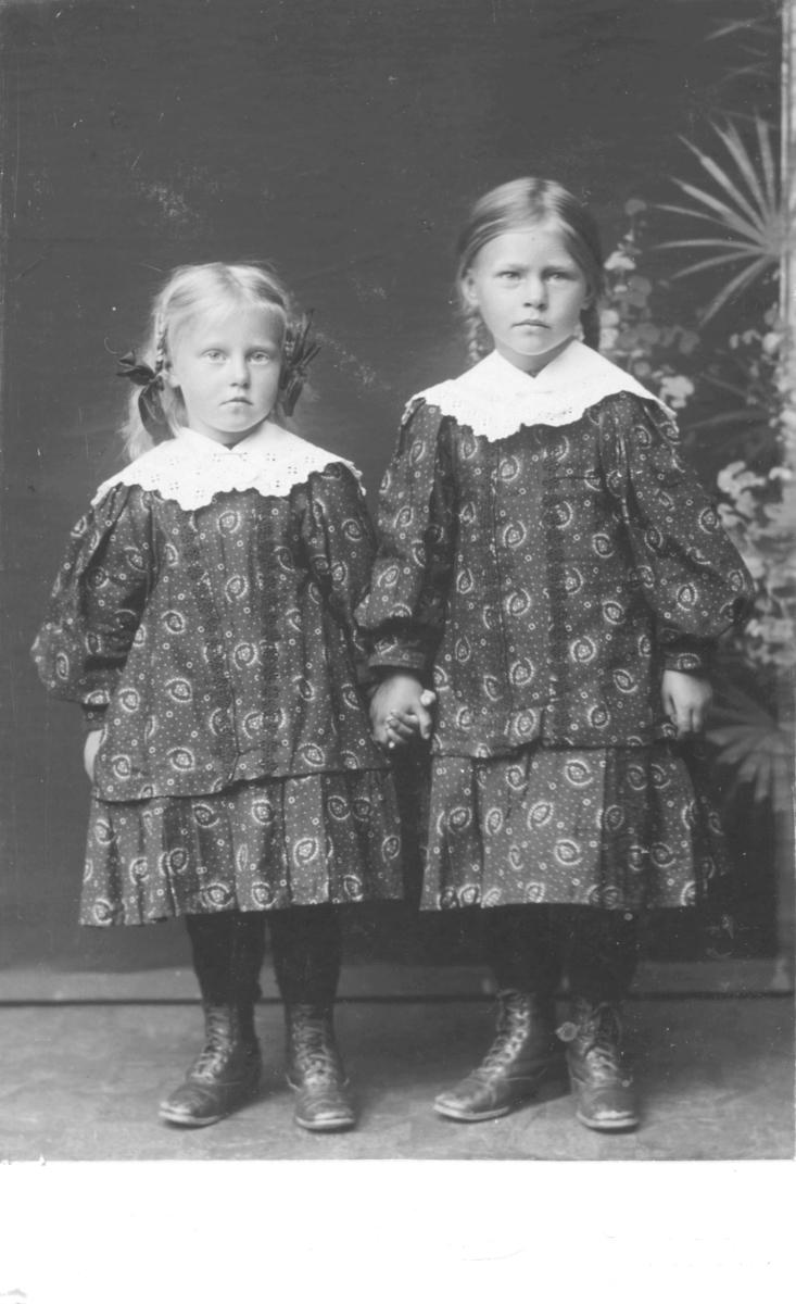 Portrett av to jenter, ikke navngitt, antakelig søstre siden de har like kjoler. Kjolene er mønstrete med hvite blodekraver, begge jentene har flettet hår. På føttene har de snørestøvler. Fotografert i fotostudio med en malt bakgrunn med palmer. Den minste jenta kan være ca. 5 år og den eldste ca. 7-8 år.