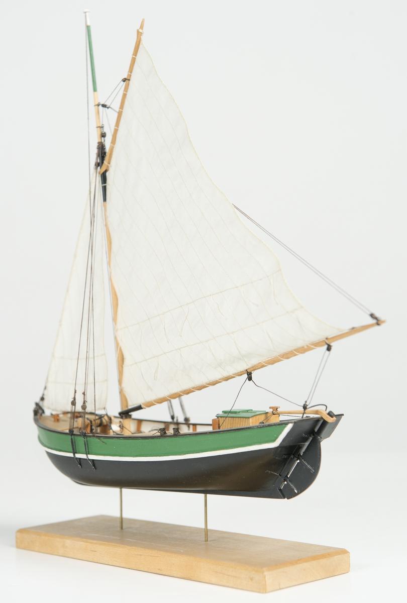 """Riggad med fock och gaffelstorsegel. Svart skrov, grön bredgång. Vit kaltopp. Modellen tillverkad till utställningen """"Seglande kungar, kungliga seglare"""", KSSS 150-årsjubileum 1980."""