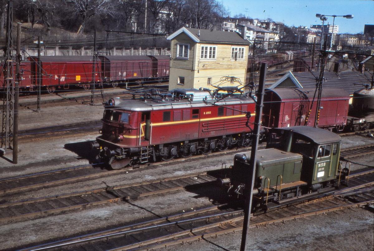 NSB elektrisk lokomotiv El 8 2065 og skinnetraktor skd 220c på Filipstad. Vi ser også stillverksbygningen der togekspeditør holder.