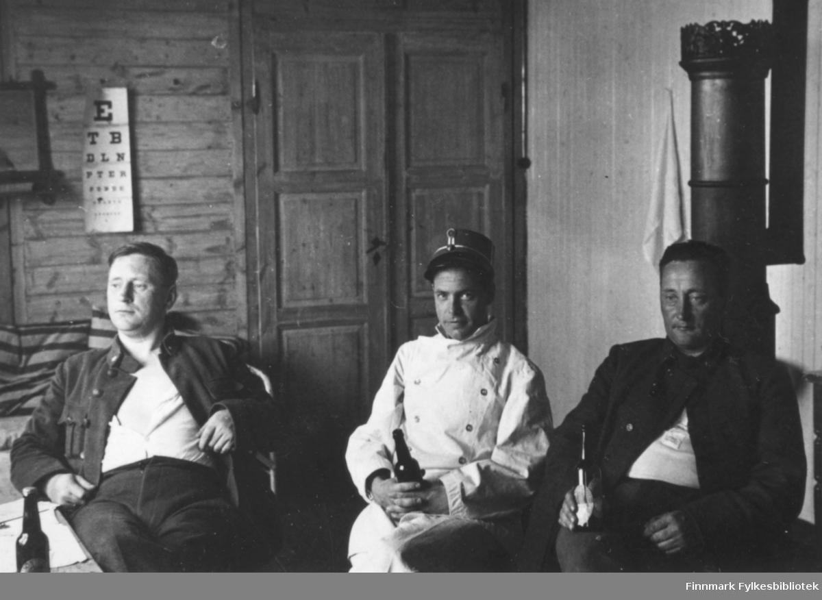 Tre menn slapper av inne på sykestua. I bakgrunnen henger en synstest-plakat. Innskrift i album: De har det bra