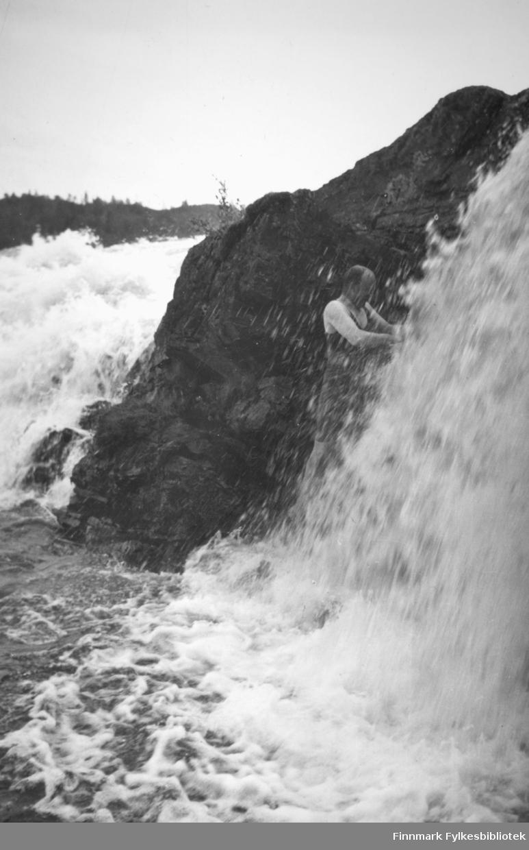 """Fra Adamsfossen, person ukjent.  Bak fotografiet står det skrevet: """"Morgendusj under Skogfoss, Pasvik, 1938"""". Bildet er fra Nord-Norges Turisttrafikk-Forbund, Harstad. Foto: ukjent."""
