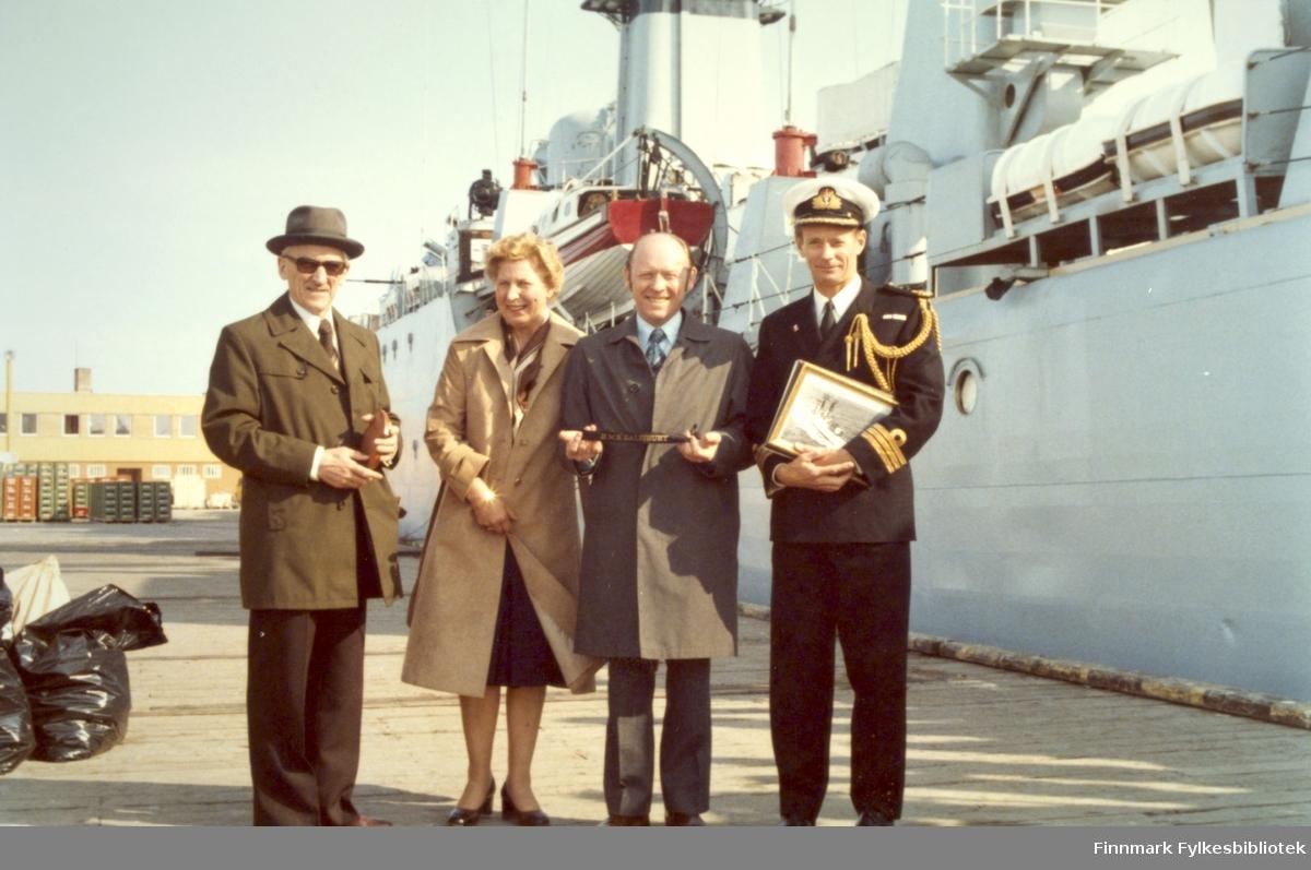 """Skipssjefen på HMS """"Salisbury"""" inviterte gjester til lunsj ombord 18.mai 1978. Bildet viser de smilende gjestene etter lunsjen.   Fra venstre: Konrad Stormark (som var sokneprest og prost på 1970-tallet), Sigrid Rasmumssen, ordfører Roger Jenssen og Commander David Brittan fra den britiske ambassade. Foto tatt av Per Bjørgan, som også deltok på lunsjen."""