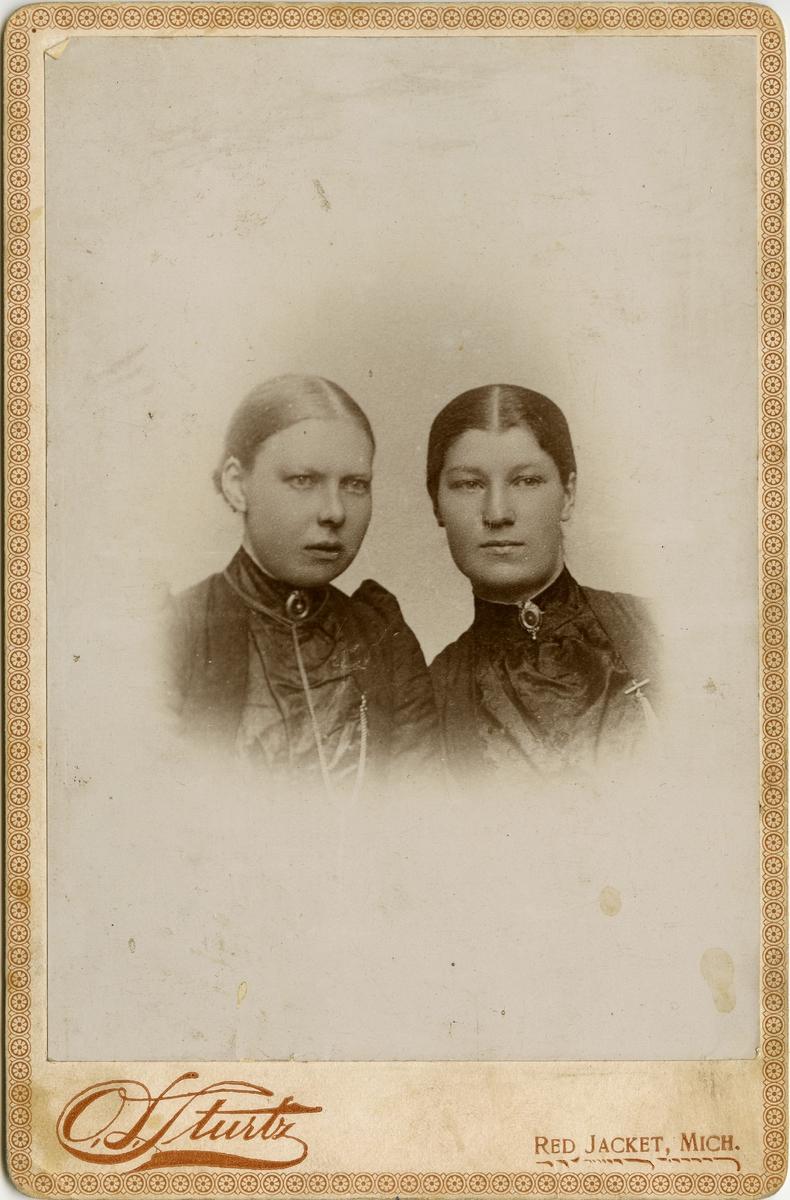 Halvfigursportrett av to unge kvinner, Hilda Niva og Selma Methi. Damene er kvener fra Vadsø som emigrerte til Michigan, Usa, i 1870-årene