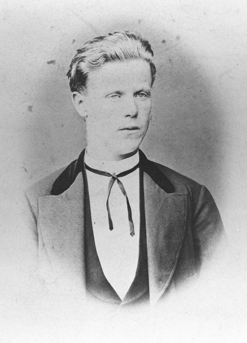 Portrett fra en ung mann. Han er kledd i dress med hvit skjorte og sløyfe. Bildet er kopiert i ovalform. Dette bildet er gammel, ca fra 1860. Tatt av Knut Wiste trolig i Bodø