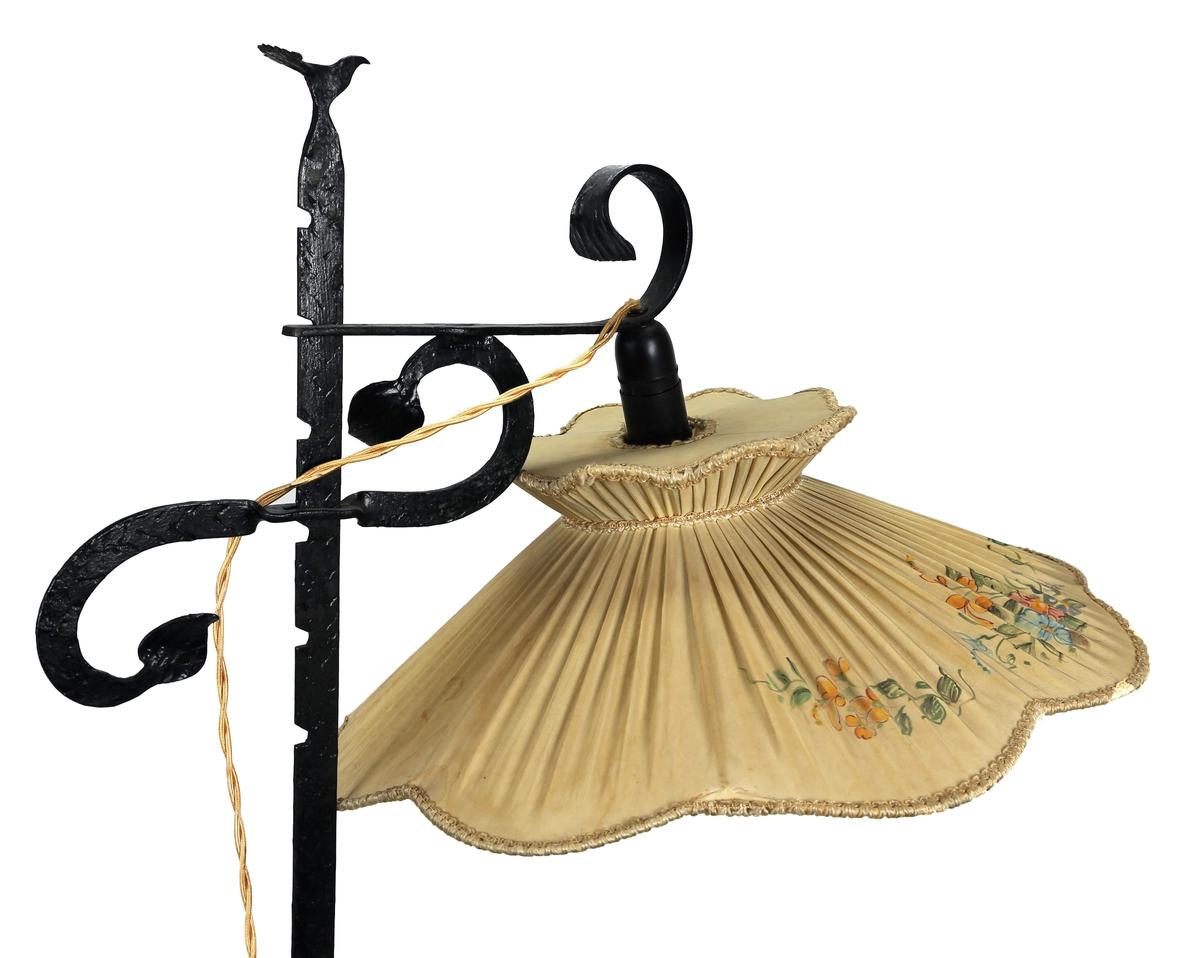 Stålampe med stativ av jern/stål med fire bein og smijernsdekor. I toppen er det smidd en storfugl. Skjermen består av malt ståltråd som er trukket med stoff og dekorert med blomstermotiv. Bryteren er en vrider som sitter like over pæra. Ledningen består av to ledninger som er tvunnet.
