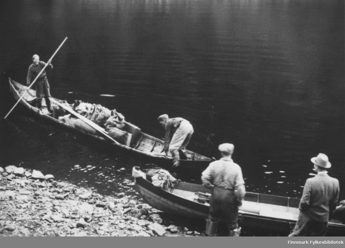 Elvebåtstaking på Altaelva. Vi ser to elvebåter hvorav en ligger tom på stranda. I den andre ser vi to menn. En står og staker og den andre er i ferd med å stige ut av eller opp i båten. På elvebredden står to menn og følger med; en i arbeidsklær, og en i dress og hatt