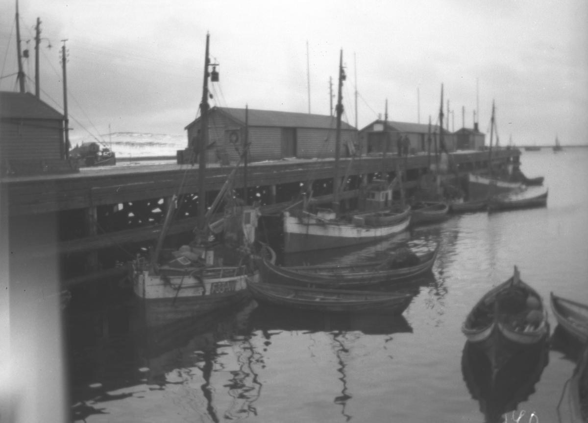 En del fiskebåter ligger langs Dampskipskaia i Vadsø og noen robåter ligger fortøyd litt utpå vannet.