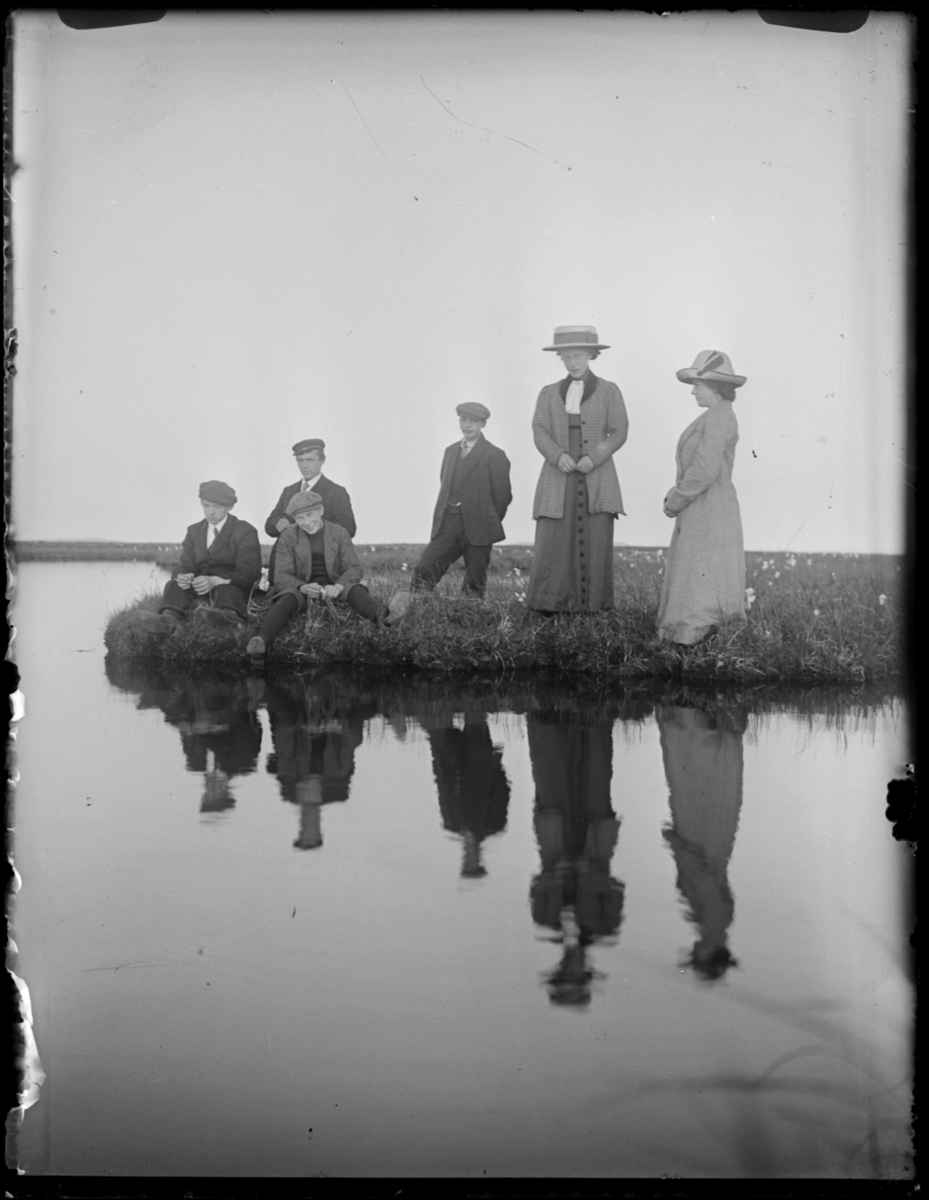 Fire unge menn, en voksen mann og to kvinner ved et vann. Det er helt stille, og speilbildet deres er svært tydelig i vannflata. Landskapet er flatt og det vokser myrull i vannkanten