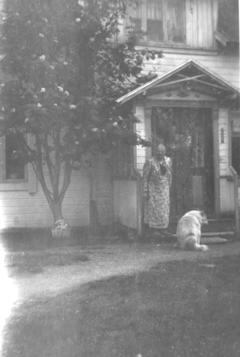 En dame med en lys hund står foran innganegen til et hus. Ved siden av inngangen et stort tre.