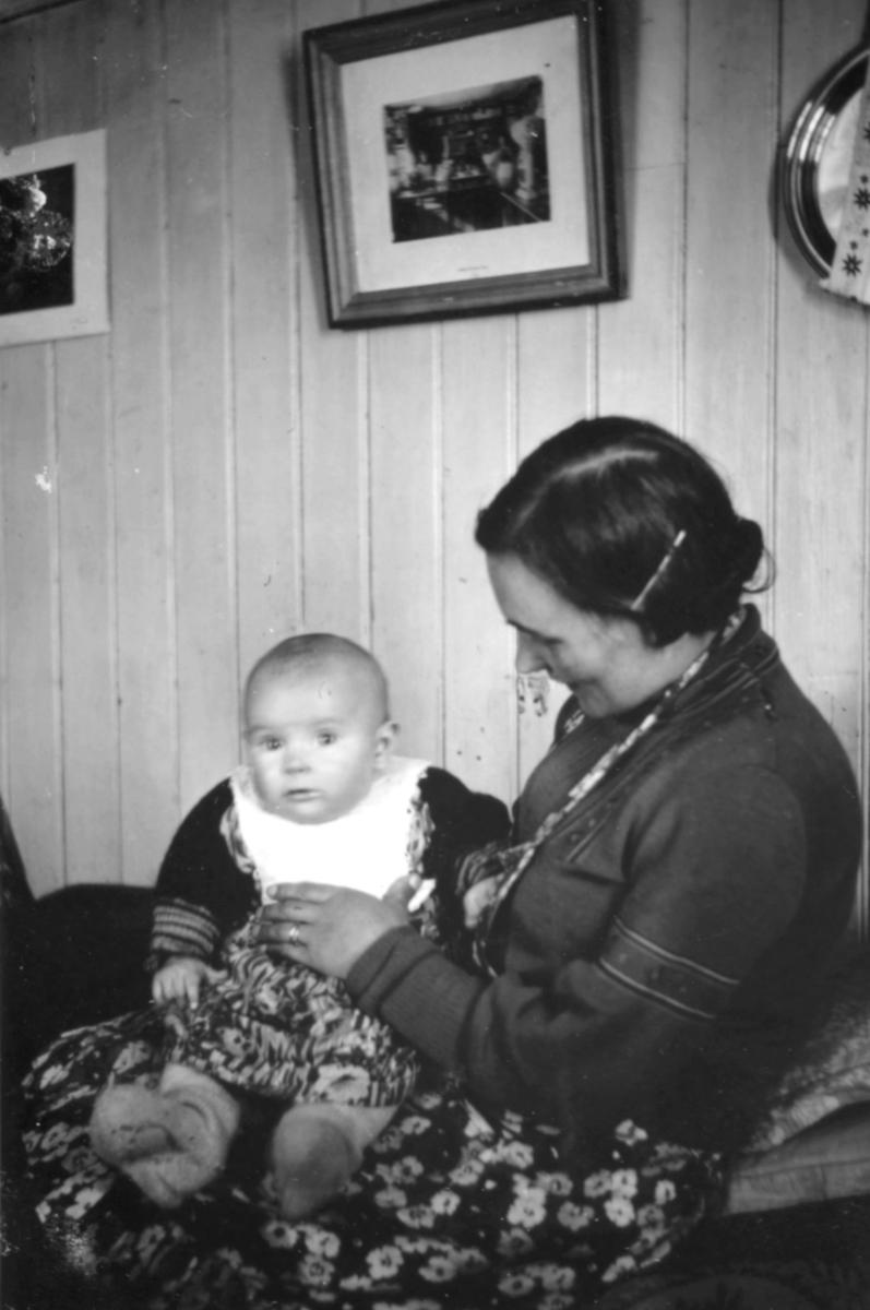 En dame sitter med en baby på fanget. Damen har mørk jakke og blomstret skjørt på seg.Babyen har en stor hvit krave rundt halsen.På veggen bak henger det bilder.