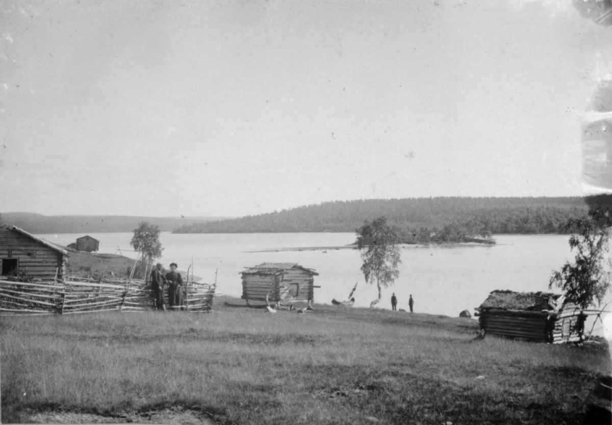 Tømmerbygninger og enger ved Vaggetem. En mann og en kvinne ved skigarden til venstre. Nede ved vannet ligger en elvebåt pyntet med flagg, og to menn står ved bredden