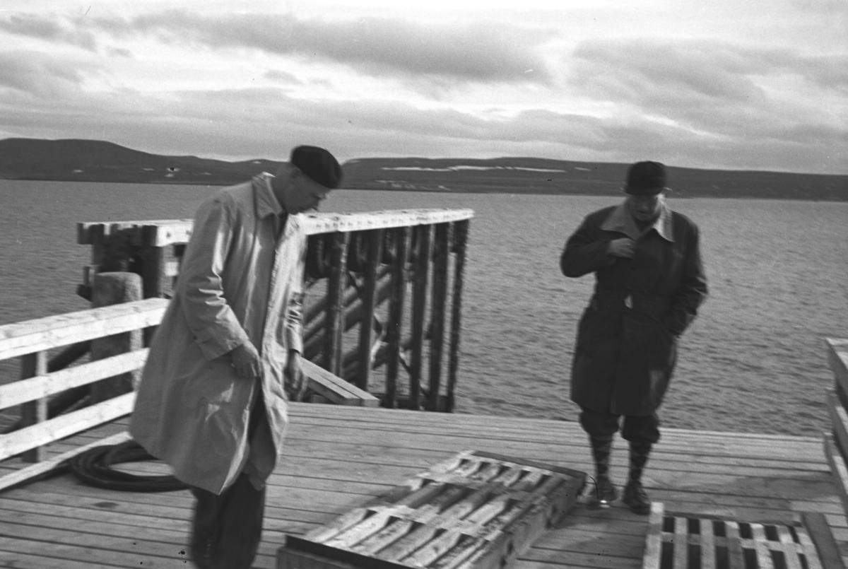 To ukjente menn på det gamle fergeleiet på Vardø-siden. Fergetrafikken begynte i 1959 og ferga hette Røsand.