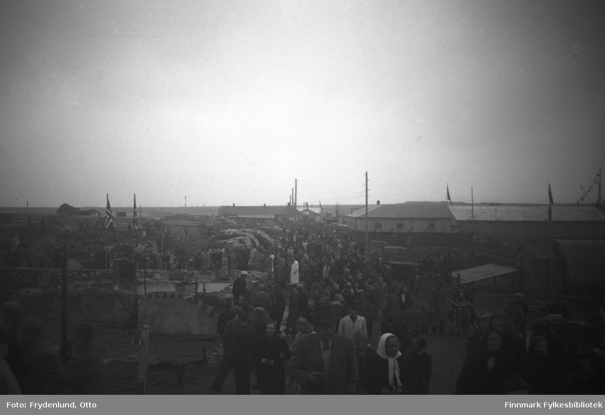 Folkevrimmel blant ruiner og nyreiste hus i sentrum av Vadsø da Kong Haakon VII besøkte byen 12. juli 1946