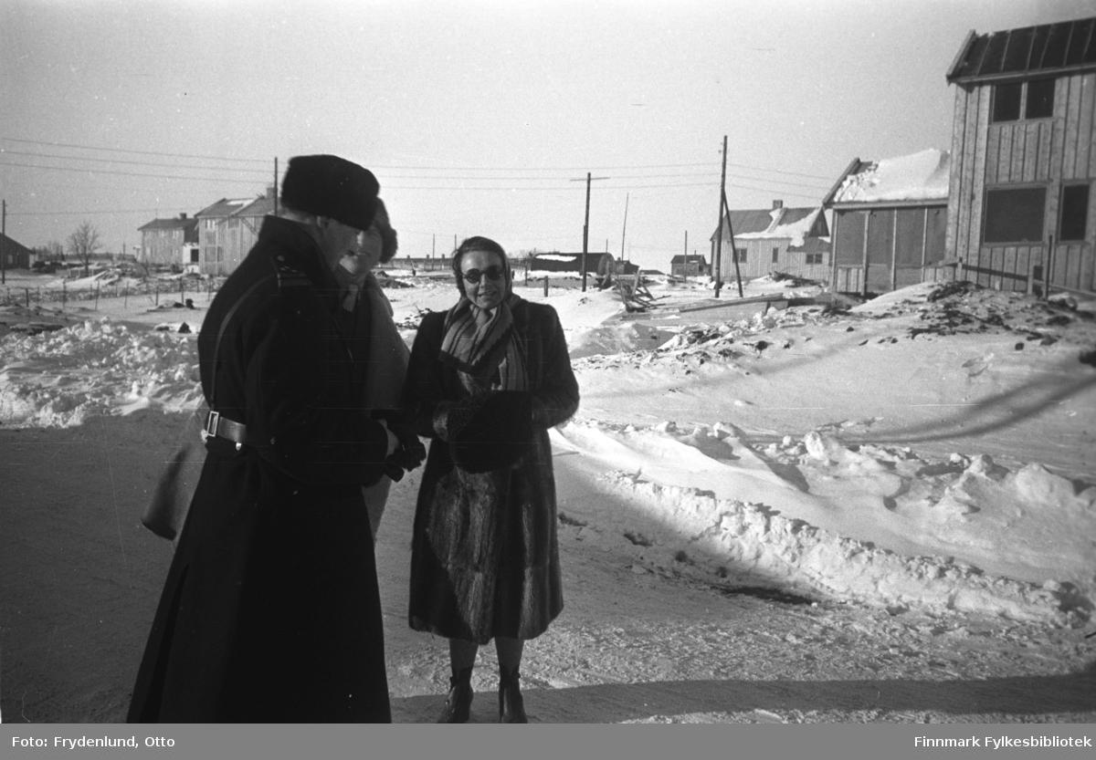 Vadsø en vinterdag med sol i gjenreisningstida. På bildet tre personer, den ene er politimester, kvinnen heter fru Wahr-Hansen
