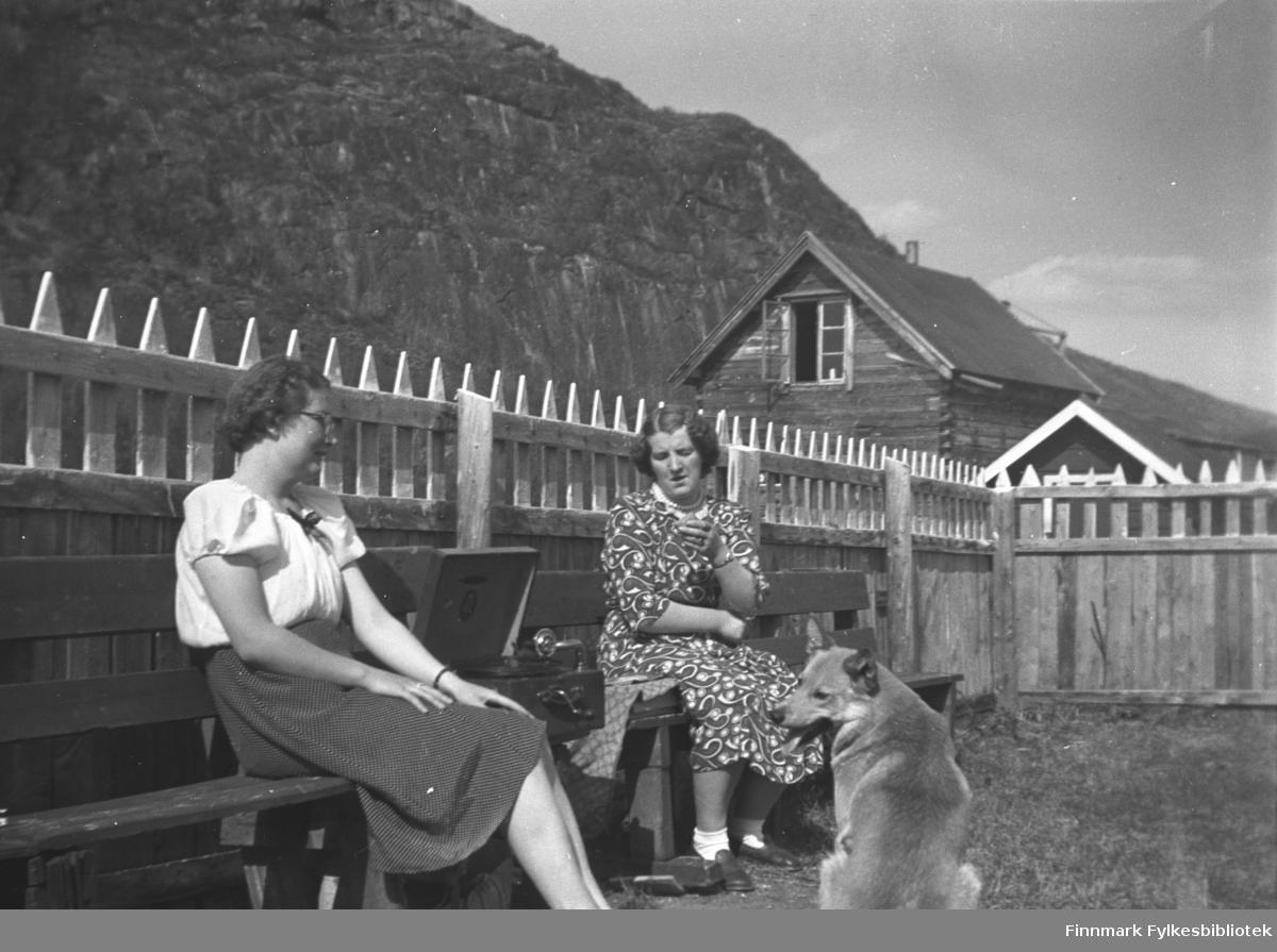 Søstrene Ingrid (til venstre) og Astrid Mikkola med sveivegrammofon i hagen på Mikkelsnes en sommerdag. Gårdshunden var også musikkinteressert