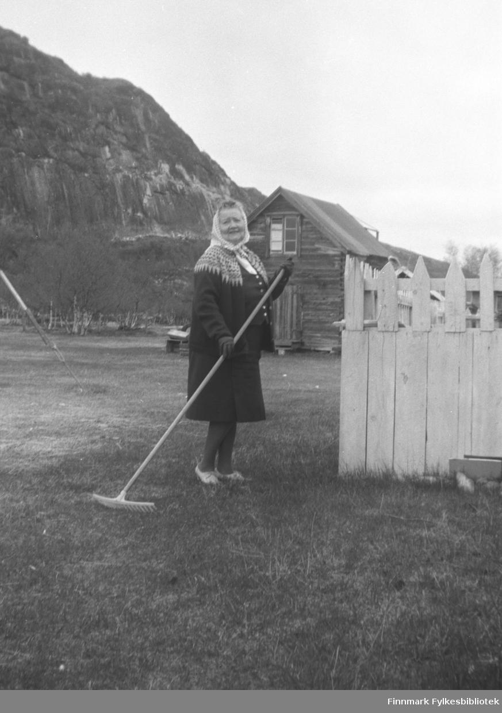 Hanna Kvandal, Kathinkas søster, med rive på gården Mikkelsnes. I bakgrunnen ser vi melkebua på gården