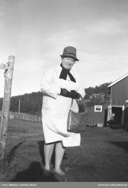 Gudrun Olsen Lie på besøk i barndomshjemmet på Mikkelsnes. I bakgrunnen ser vi fjøset med et lite påbygg. Påbygget ble brukt til lager for melfor til sauene. Dessuten var der et melkesilerom