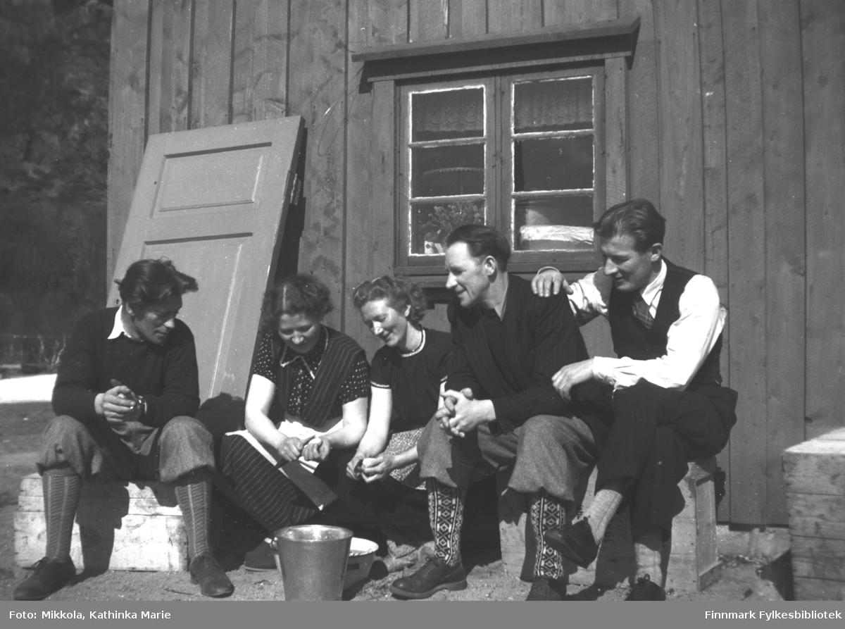 Potetskrelling ute i sola på Mikkelsnes - kvinnene arbeider og mennene prater og ser på. Fra venstre: Sverre Olsen Lie, Kari Mikkola, Marine Smuk, Per Sivle Olsen og Andreas Mikkola. Kari, Marine og Andreas var søsken, Per og Sverre var gift med to andre av Mikkola-søstrene