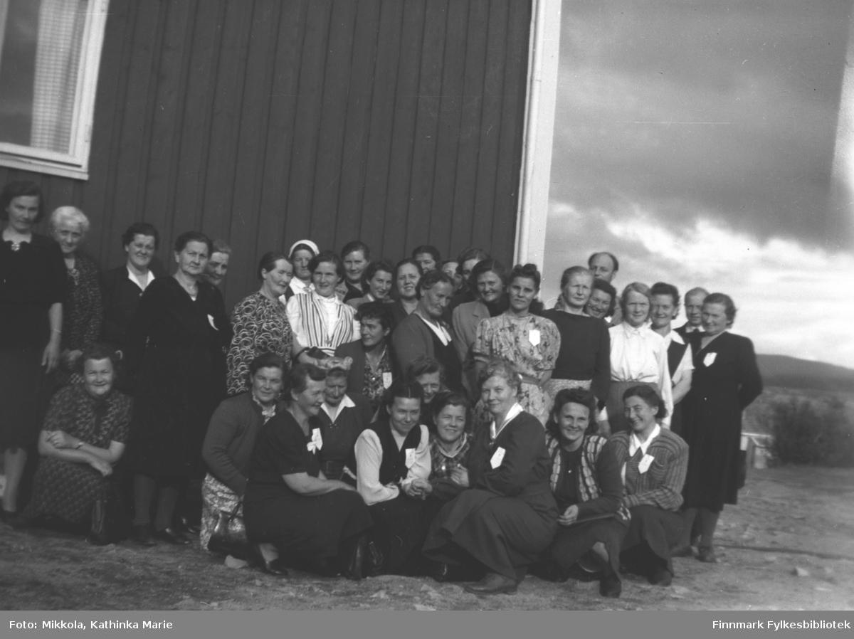 Stor gruppe kvinner samlet utenfor en bygning. Bare en mann stikker hodet fram i høyre del av bildet. Bildet er tatt fra helselagenes fylkesmøte i Lakselv. Anna Ravna m flere
