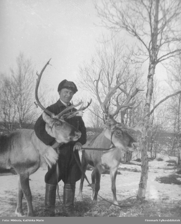 Petter Enbusk med to kjørerein tjoret til et tre. Han har skinnlue og piekso.