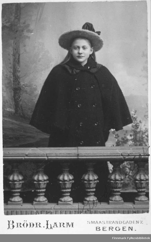 Portrett av en ung dame. Hun har en hatt med bred brem og en mørk kappe på seg. Hun står bak et lite, lavt rekkverk. De små stolpene i rekkverket har utskjæringer. Portrettet er tatt hos Brødrene Larm i Bergen.