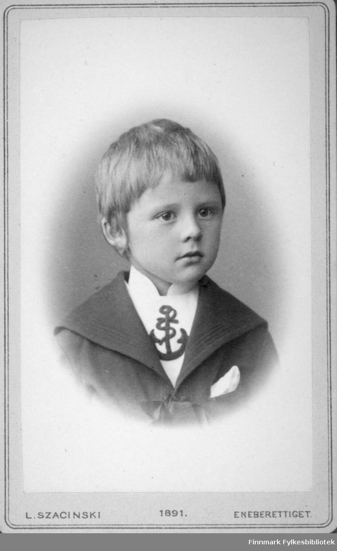 Portrett av en gutt. Han har en mørk jakke med bred krage og lommetørkle i brystlomma. Den hvite skjorta hans har et ankermønster foran. Portrettet er tatt hos kgl. hoffotograf L. Szacinski i Christiania.