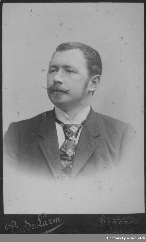 Portrett av en mann iført en ganske mørk dressjakke. Han har hvit skjorte og et mønstret slips.