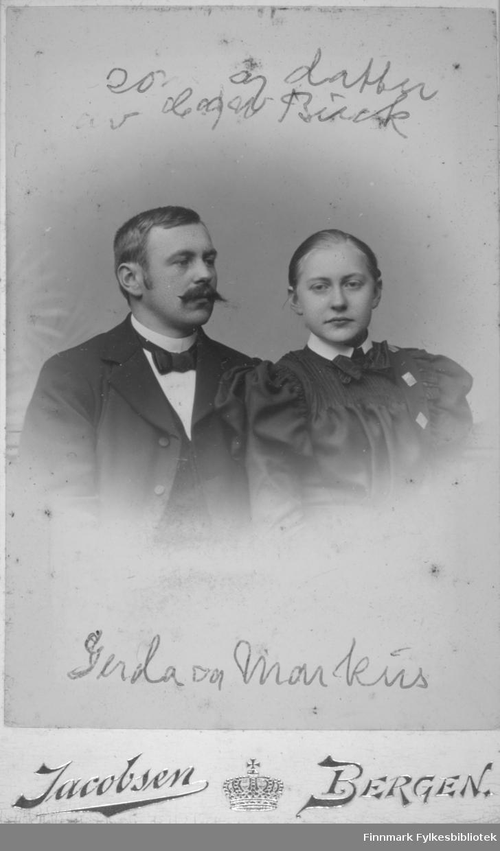Portrett av søskene Markus og Gerda Buck. Han har en mørk dressjakke, hvit skjorte og sløyfe i halsen. Hun har en mørk overdel, hvit krage og sannsynligvis smykker hengende på venstre side av brystet.