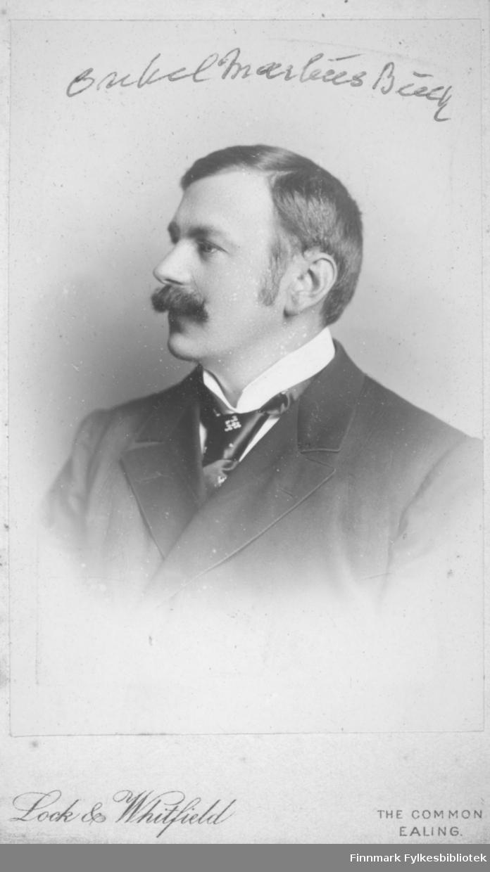 Portrett av Markus Buck. Han har en mørk dressjakke, hvit skjorte og slips på seg.