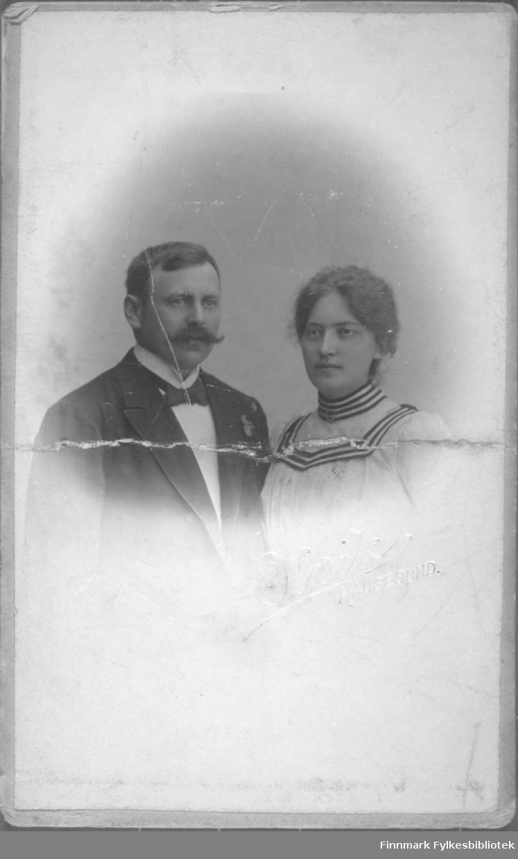 Portrett av en mann og en kvinne. Mannen har mørk dressjakke, hvit skjorte og slips på seg. Kvinnen har en lys bluse med mørke striper på kragen.