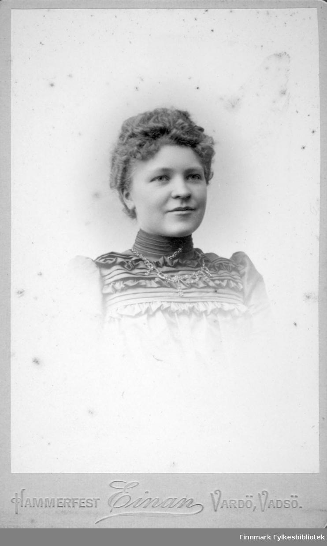 Portrett av en dame iført en ganske lys bluse med en høy hals. Et smykke henger rundt halsen hennes.
